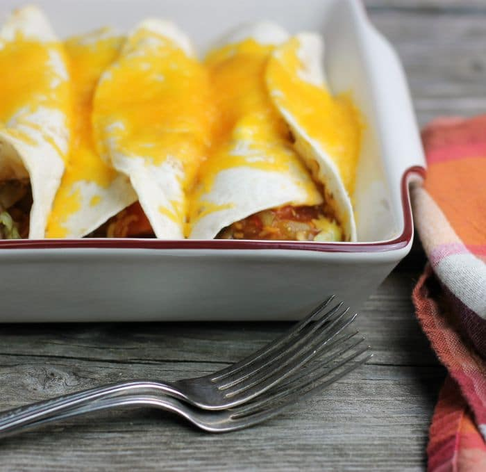 Easy beef enchiladas are stuffed full of ground beef, refried beans, chilis, tomatoes, shredded lettuce, cheese, and enchilada sauce they are full of flavor and easy to make.