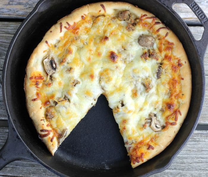 Skillet Sausage and Mushroom Pizza, made in cast iron skillet which makes for a soft chewy crust and then topped with sausage, mushrooms, and mozzarella cheese.