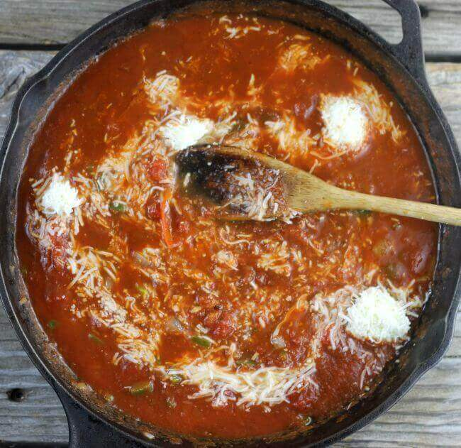 Cast iron skillet with tomato sauce and mozzarella cheese with wooden spoon