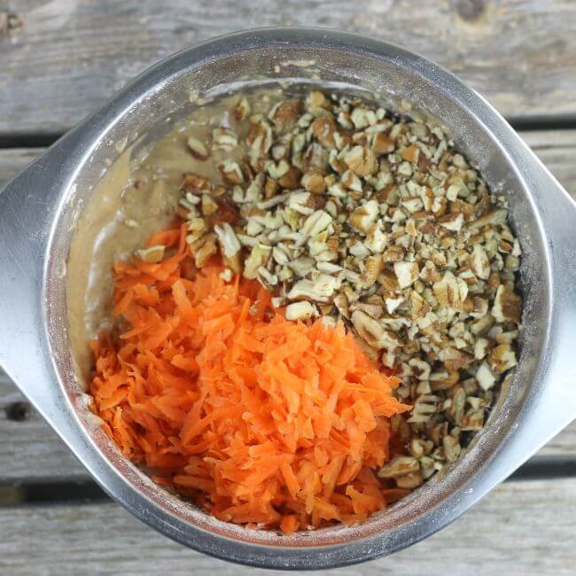 Shredded carrots and pecans in a stainless steel mixing bowl.