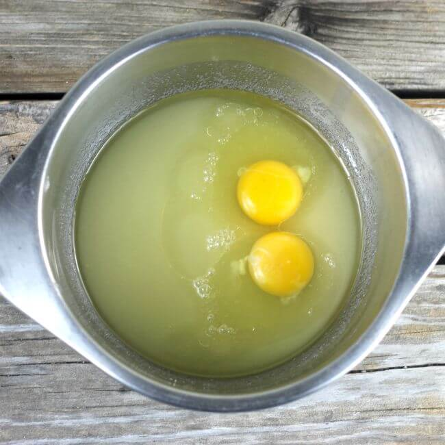 Eggs and sugar in a stainless steel mixing bowl.