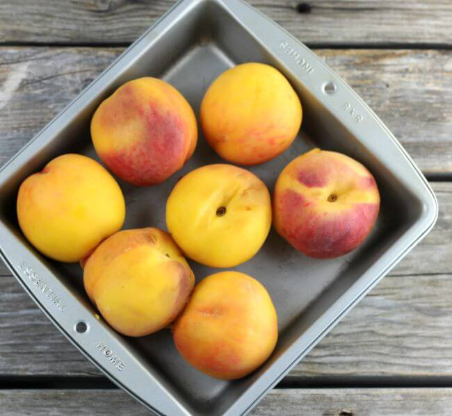 A baking pan filled with peaches.