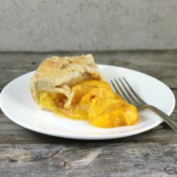 A slice of peach galette on a white plate with fork on side.