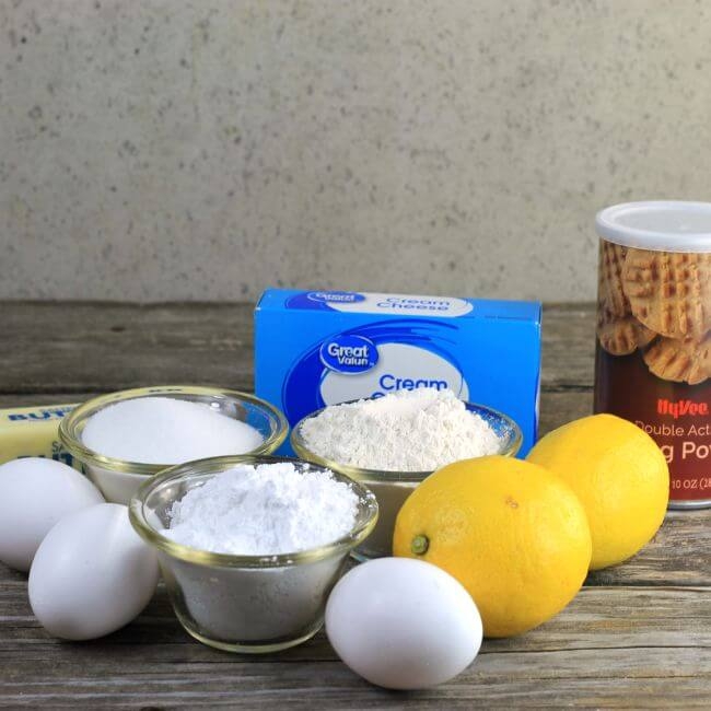 Eggs, butter, cream cheese, flour and sugar in bowls, can of baking powder, and lemons.