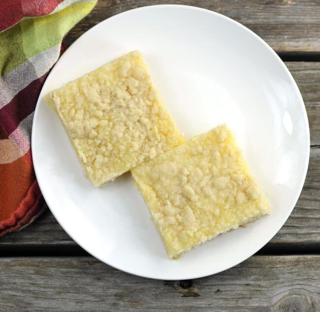 Two lemon bars setting on a white plate.