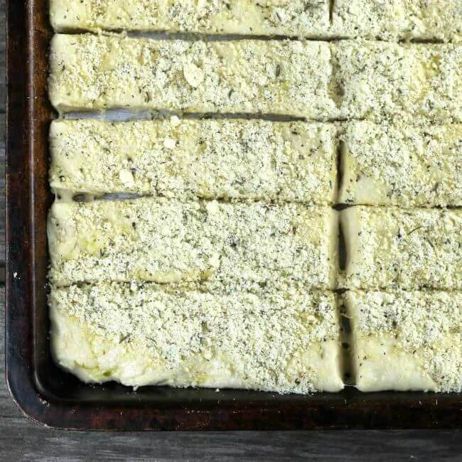 Unbaked bread sticks in a sheetpan