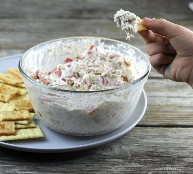 Pepperoni dip with hand holding a cracker with dip on it.