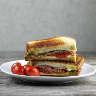 Pesto grilled cheese with salami with cherry tomatoes on a white plate.