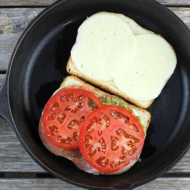 2 pieces of bread topped with cheese, pesto and tomato in skillet.