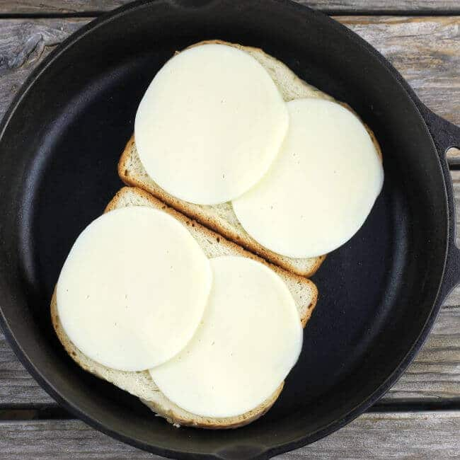 2 slices of bread topped with cheese in cast-iron skillet.
