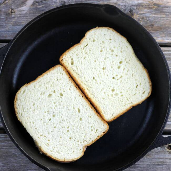 Two slices of bread in cast-iron skillet.