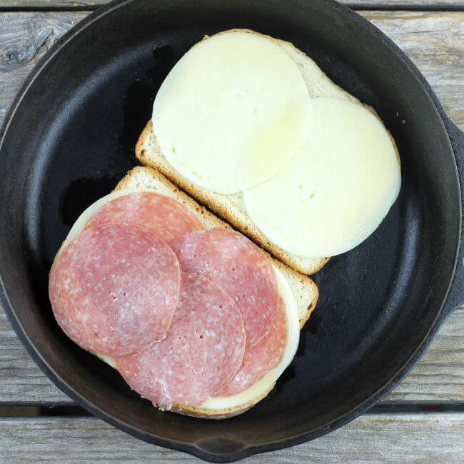 2 slices of bread with cheese and salami in skillet.