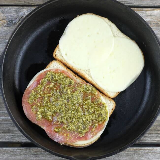 2 slices of bread with cheese, salami, and pesto in skillet.