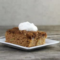 Apple cake topped with whipped cream on white plate.