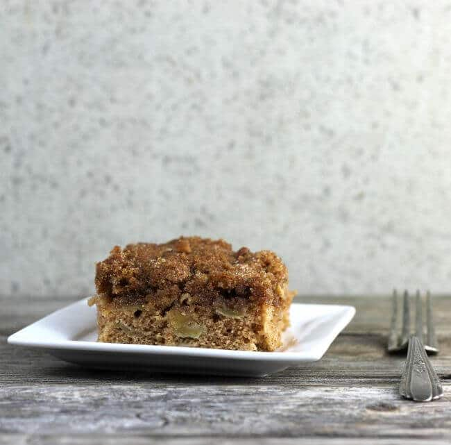 Apple cake on white plate with fork on the side.