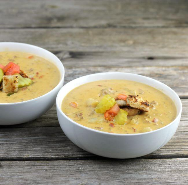 Two bowls of cheeseburger soup in with bowls.