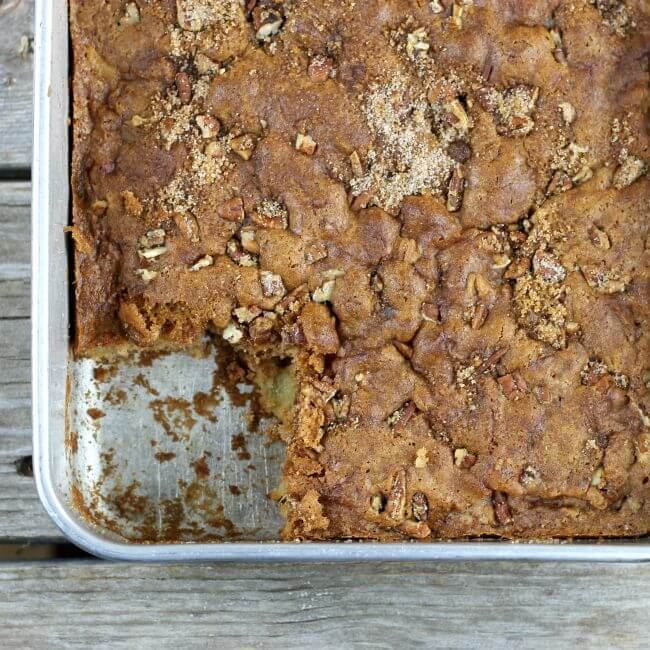 A piece of apple cake missing from the baking pan.