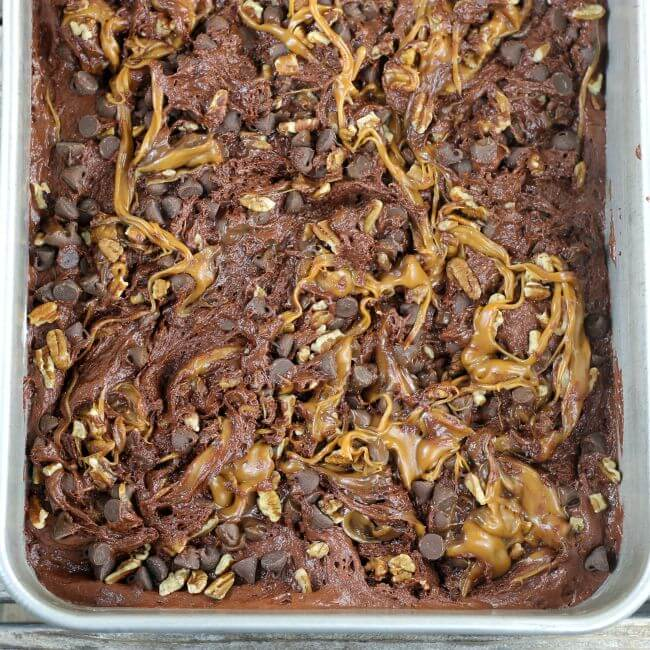 Turtle cake batter with chocolate chips, pecans, caramel swirled into the batter in a baking pan.