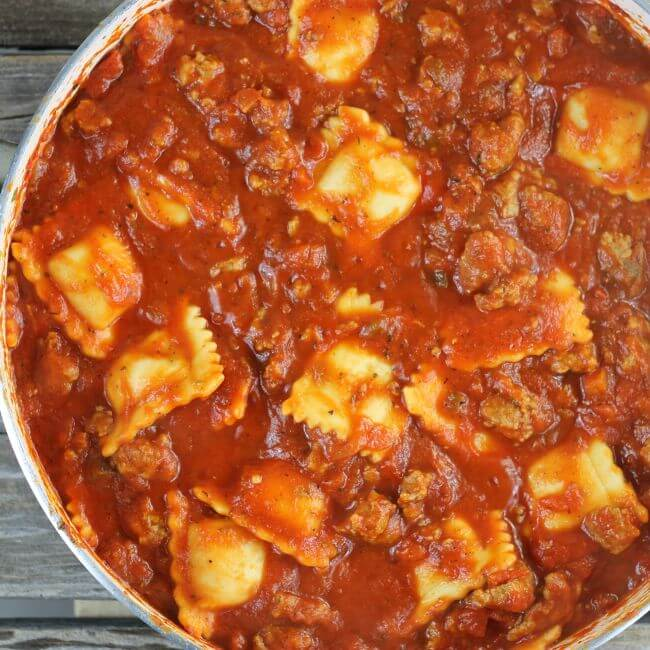 Cooked ravioli in meat sauce in a skillet.