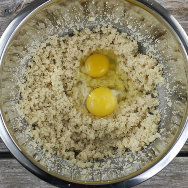 Eggs add to wet ingredients of apple cake in bowl.