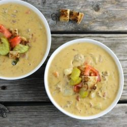 Two bowls of cheeseburger soup. with tomatoes, pickles, and croutons on top.