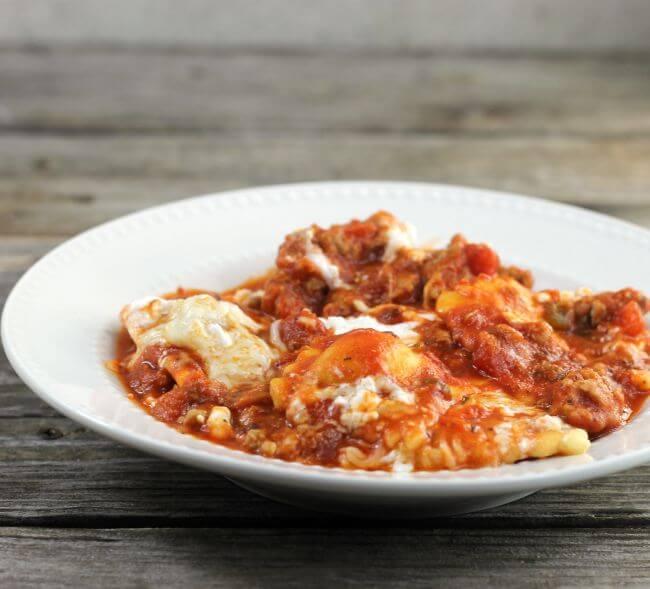 Skillet ravioli lasagna in a white bowl.