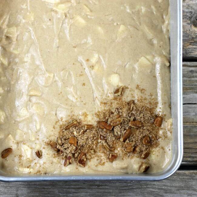 Cake batter in baking pan starting sprinkle on topping.