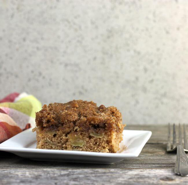 Apple cake on a white plate with plaid napkin and fork