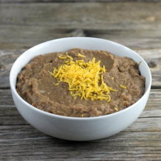 Refried beans topped with cheddar cheese in a white bowl.