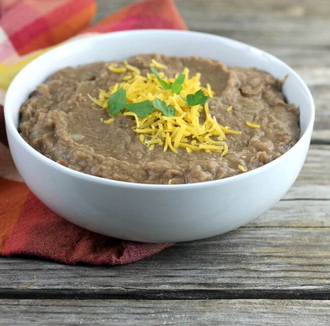 Refried beans topped with cheese and cilantro in a white bowl.
