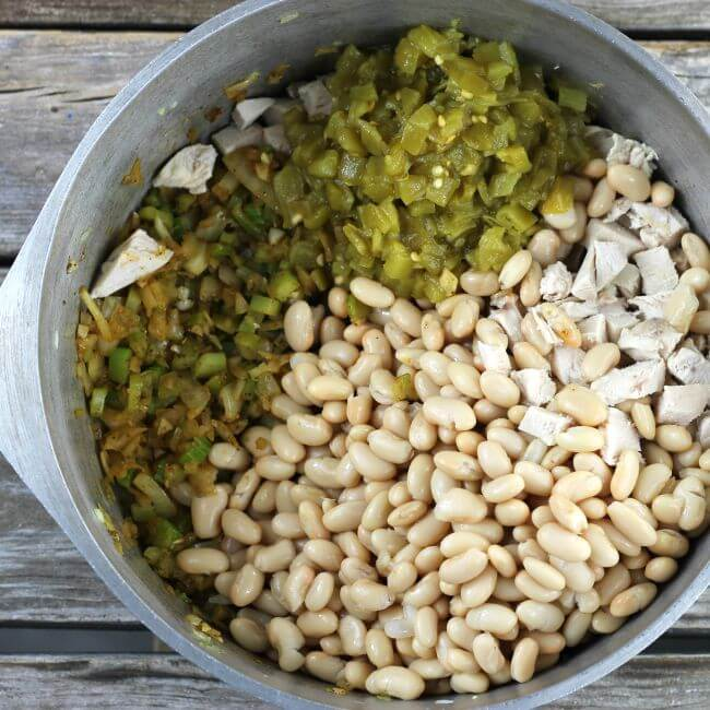 White beans, chicken, green chiles in a Dutch oven.
