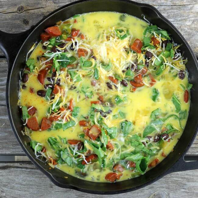 Eggs, chorizo, spinach, black beans, in a cast-iron skillet.