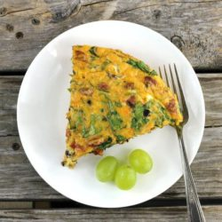 A slice of a chorizo frittata with a green grapes and a fork on a white plate.