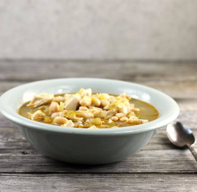 White chicken chili in a green bowl with sppon by the side of the bowl.