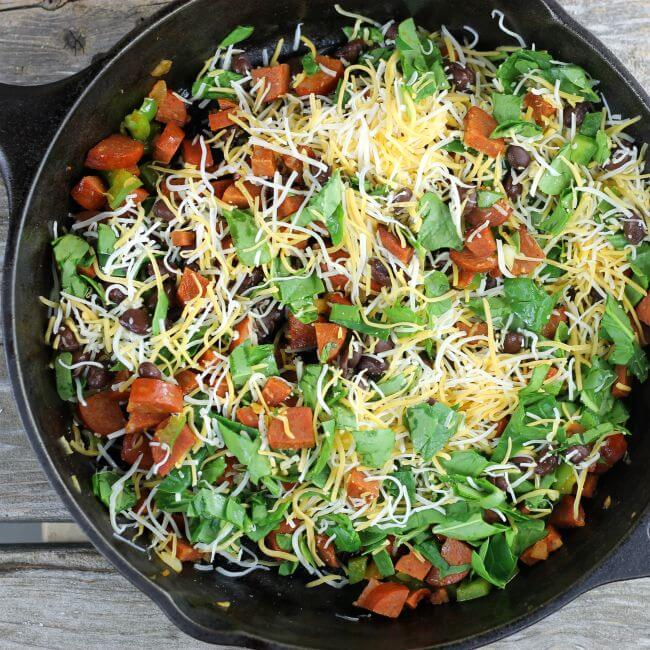 Chorizo, spinach, black beans, and cheese in a cast-iron skillet.