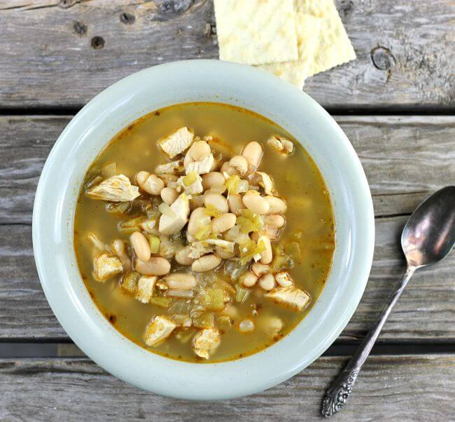 White chicken chili in a green bowl with crackers and spoon on the side.