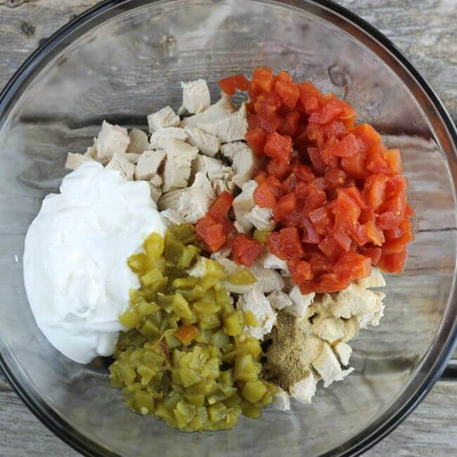Chicken, green chiles, diced tomatoes, and sour cream in glass bowl.