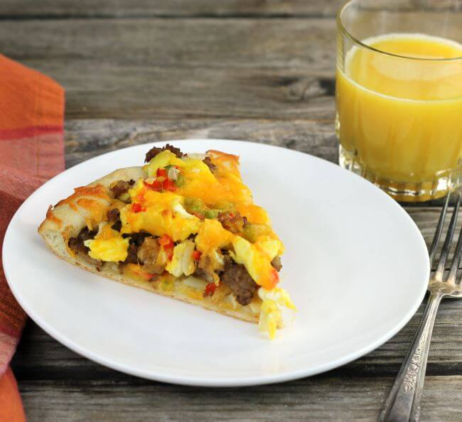 A slice of sauasage breakfast pizza on a white plate with a napkin, fork, and a glass of orange juice on the side.