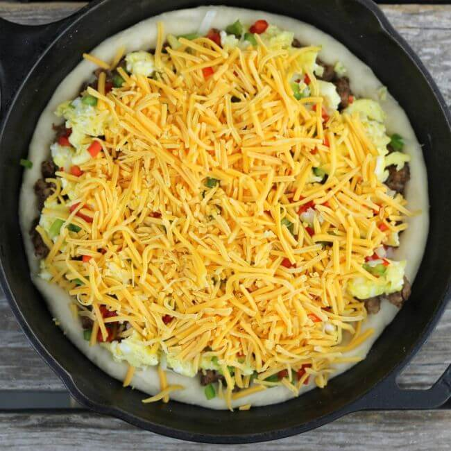 Sausage breakfast pizza with cheddar cheese spread over top of the eggs, sausage, and vegetables in the skillet.