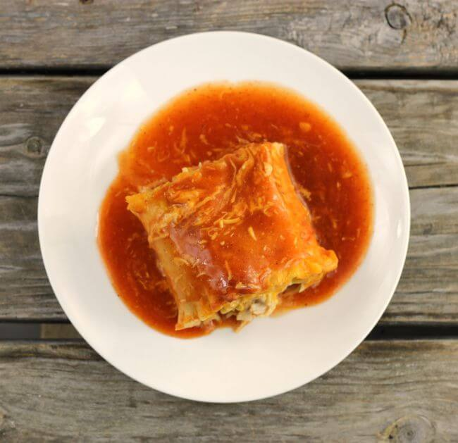 Chicken enchilada lasagna roll-up in red enchilada sauce on a white plate.