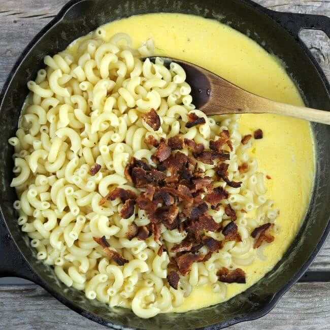Macaroni and bacon added to the cheese sauce in a skillet.