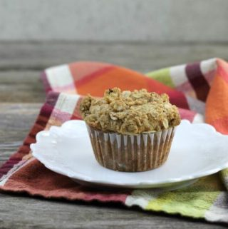 Best banana muffin on a white plate set on a napkin.