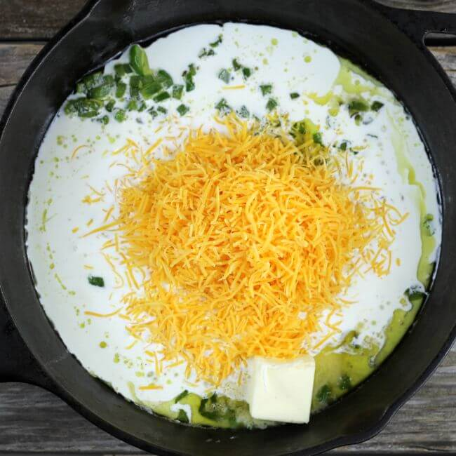 Cream and cheese added to the green pepper in the cast-iron skillet