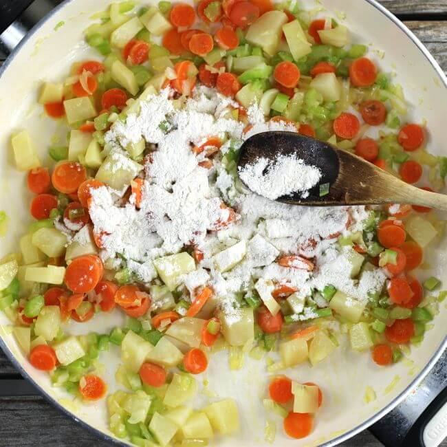 Flour added to the cooked vegetables in a skillet.