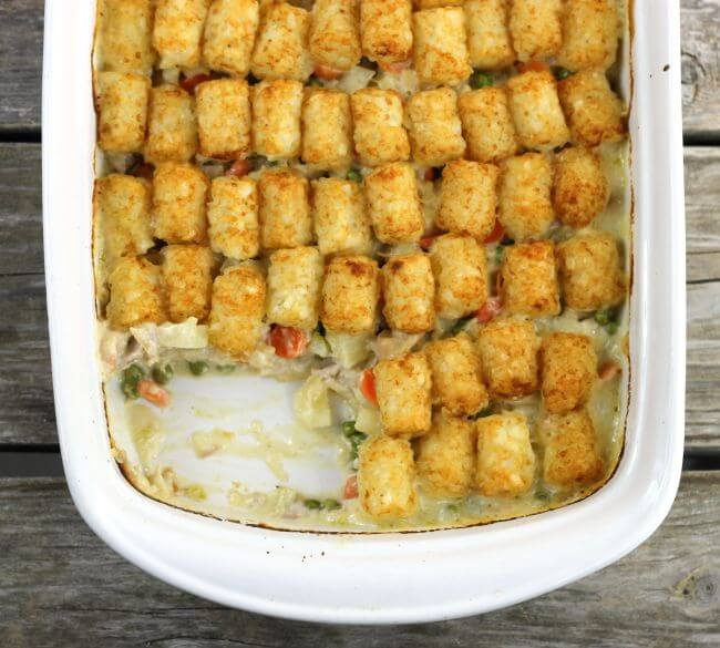 Tater Tot Chicken Casserole in baking pan with one serving removed.