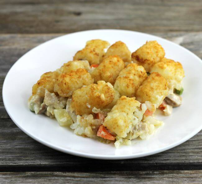 Side view of the tater tot chicken pot pie casserole on a white plate.