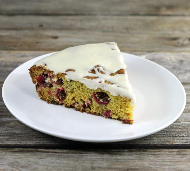 A slice of cranberry cake on a white plate.