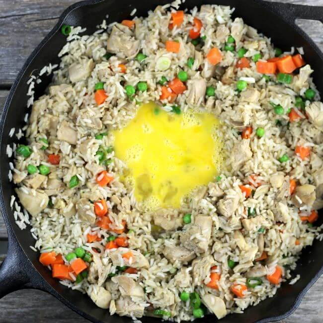 Make a well in the rice and add the beaten egg in the skillet.