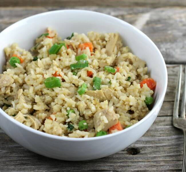 Fried rice in a white bowl with a fork on the side.