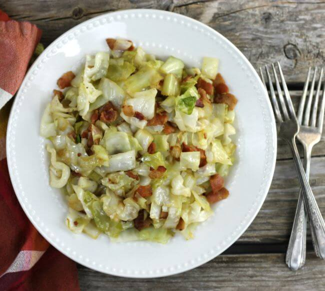 Cabbage in a white dish with a napkin and forks on the sides of the dish.